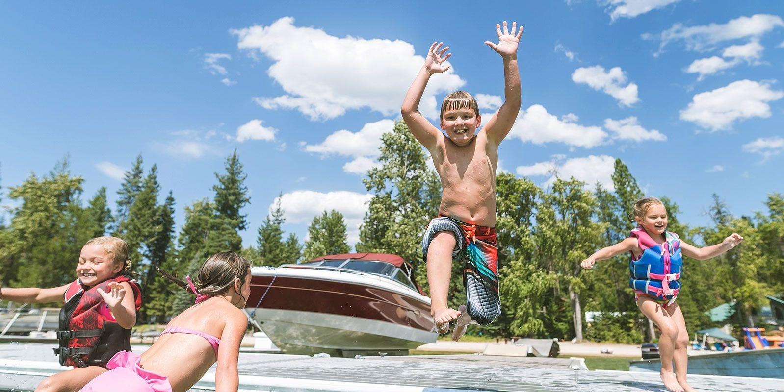 Kids having fun swimming on their home beside water